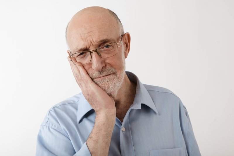 man holding jaw in pain needing root canal therapy