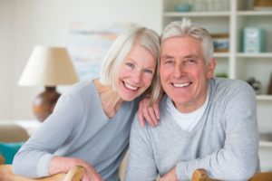 elderly couple smiling with dental implants in Tomball