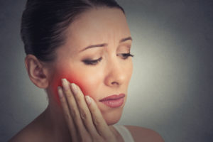 Woman with facial swelling holding hand to jaw
